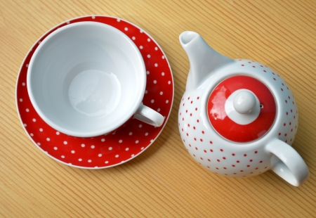 Red polka dot kettle and cup of tea Stock Photo