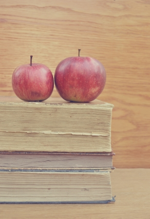 Stack of books and red apple on wooden table photo