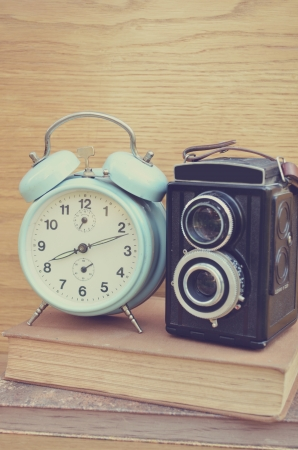 Vintage camera on book and clock Stock Photo - 23237756