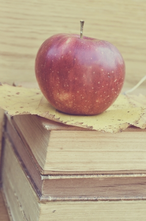 Fresh red apple on old books photo