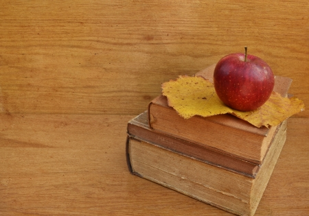 Apple on old books on wooden background photo