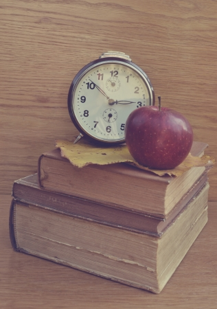Apple on old books with brown clock photo