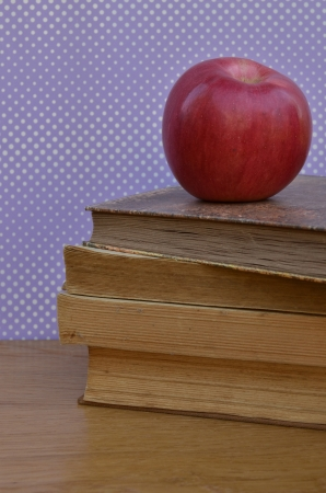 Fresh red apple on old dirty books photo