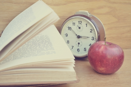 Open book and red apple on wooden table photo
