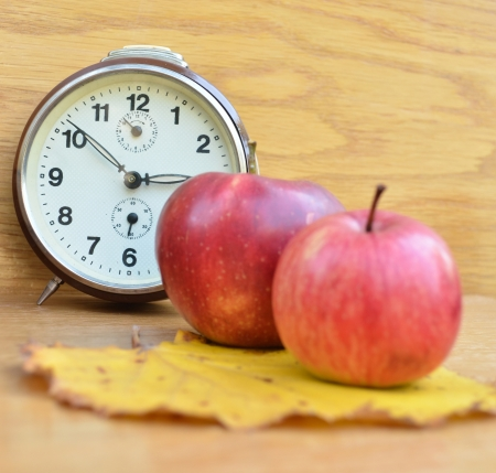 red apples and clock on wooden table photo