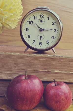 Vintage books with clock and apples photo