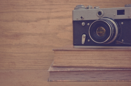 Vintage camera on book on wooden background Stock Photo - 23238696