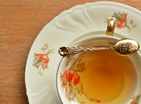 antique dishes: Cup of tea and teaspoon on wooden