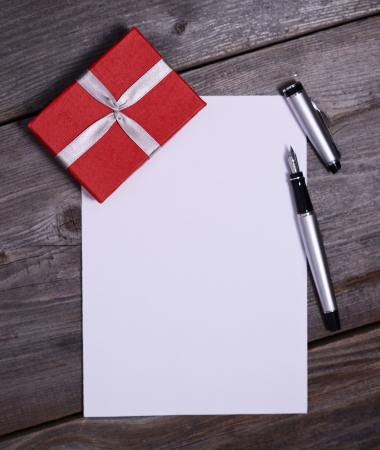 Blank paper with gift on wooden photo