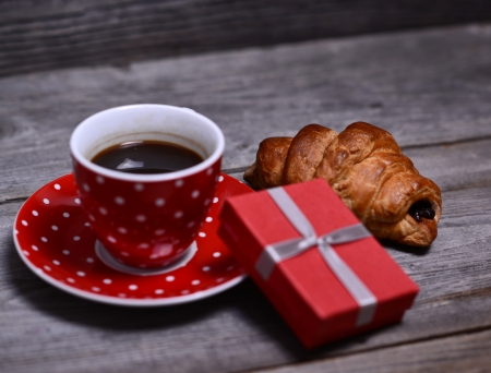 Cup of coffee with present and croissant on wooden photo