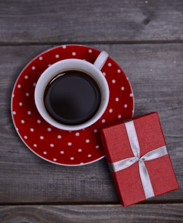 Cup of coffee with present on wooden background photo