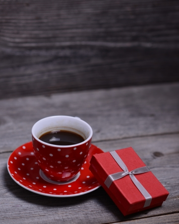 Cup of coffee with present on wooden  photo