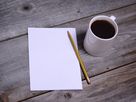 White mug of coffee and blank paper photo