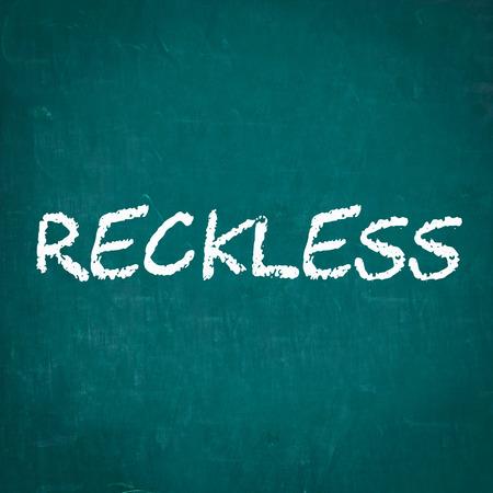 reckless: RECKLESS written on chalkboard Stock Photo