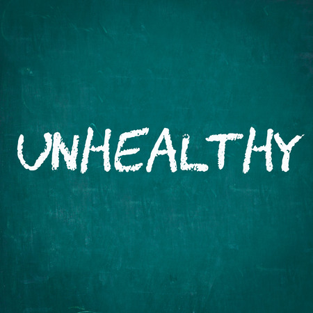 unhealthy thoughts: UNHEALTHY written on chalkboard Stock Photo