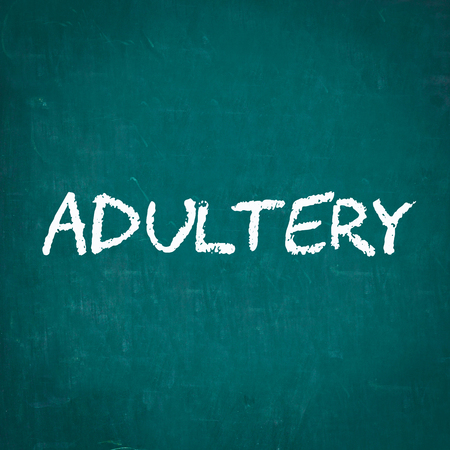 adultery: ADULTERY written on chalkboard Stock Photo