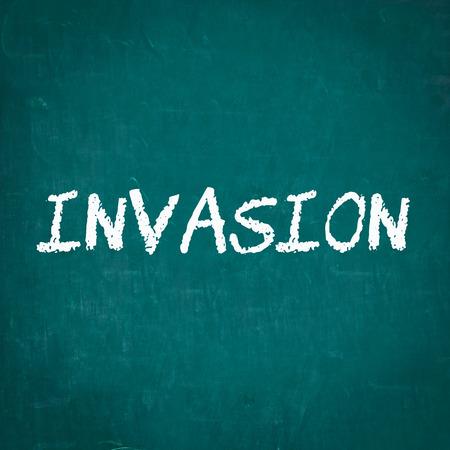 an invasion: INVASION written on chalkboard