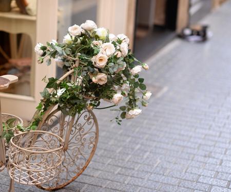 original bike: Beautiful white vintage bicycle with flowers on street