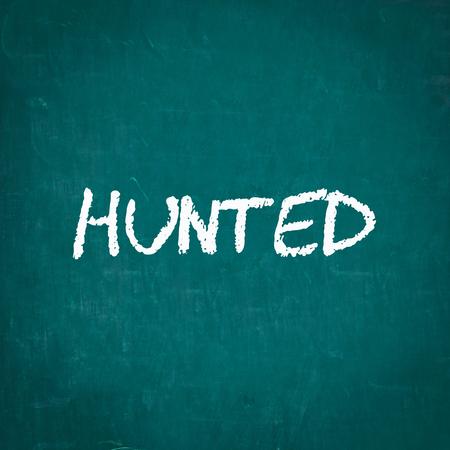 hunted: HUNTED written on chalkboard