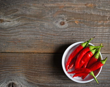 Chilly pepper on the wooden background