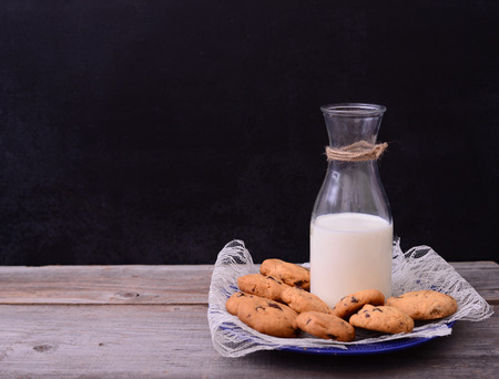 medium group of objects: Bottle of milk with cookies on rustic table Stock Photo