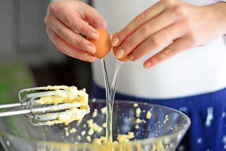 huevo blanco: Primer de un par de manos que quiebra un huevo en un tazón de vidrio