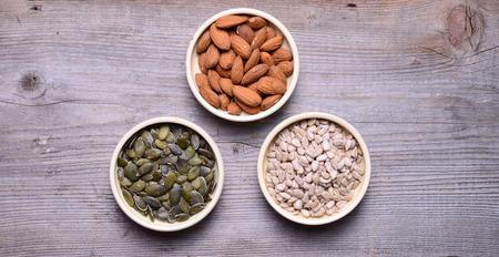 diferent: Sorted diferent seeds in white bowls on wooden background