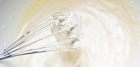 cream cake: Whipping cream with a whisk close up