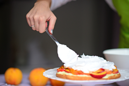 Woman hand put whipped cream on the cake crust Stok Fotoğraf