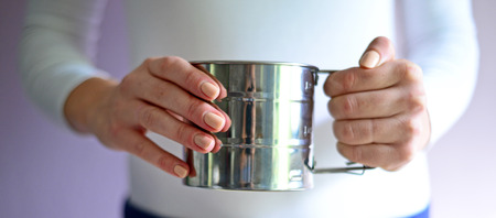 battledore: Hands with Sifting flour into a bowl Stock Photo