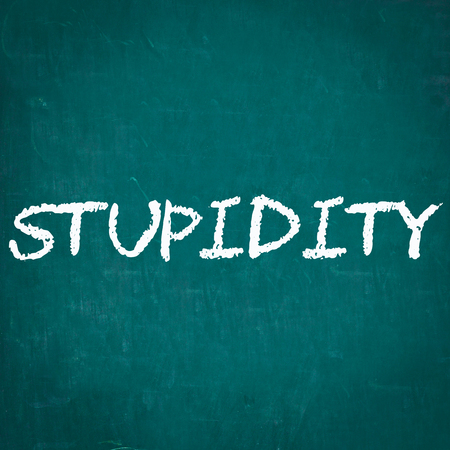 stupidity: STUPIDITY written on chalkboard Stock Photo