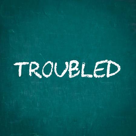 troubled: TROUBLED written on chalkboard