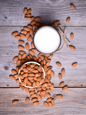 almond: Almond milk in glass with almonds in bowl, on wooden background