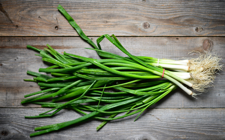 bulb and stem vegetables: Fresh spring onion on wooden background