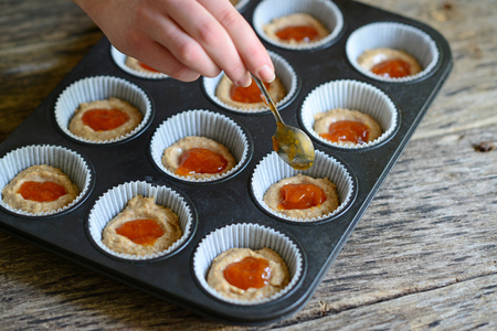 hand jam: Woman hand prepare healthy muffins with jam