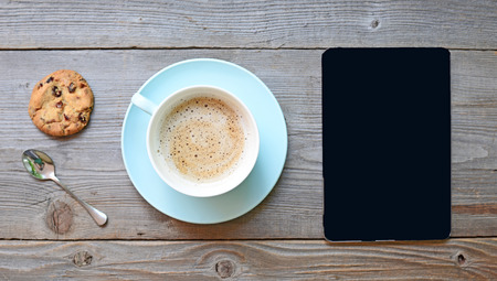 Tablet pc looking like ipad mini on table with coffee cup Stok Fotoğraf
