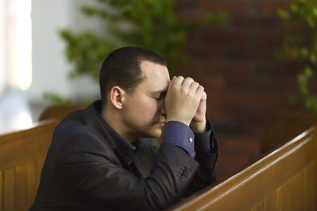 Man bidden in de kerk