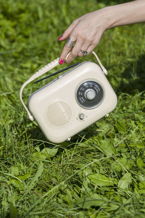 weaken: Woman holds a radio receiver in hand