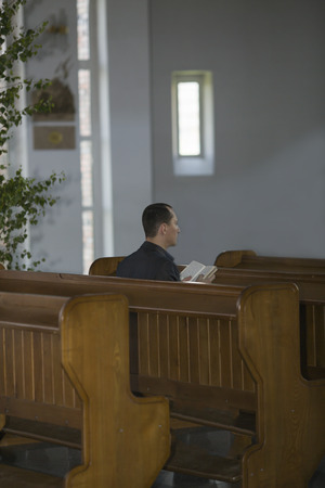 redemption: Man reading the Bible in church