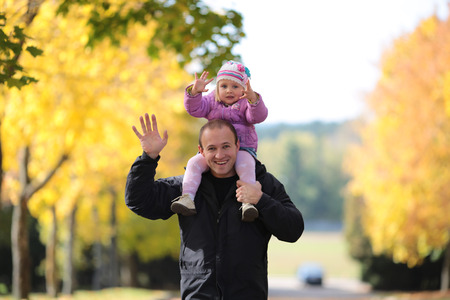 Man with a daughter collect fallen list in Park photo