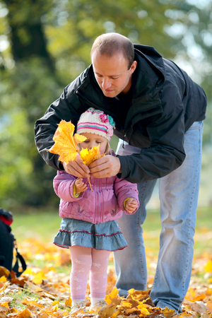 The man and the child in autumn park