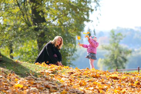 Young woman playing with a child in autumn park Stock Photo