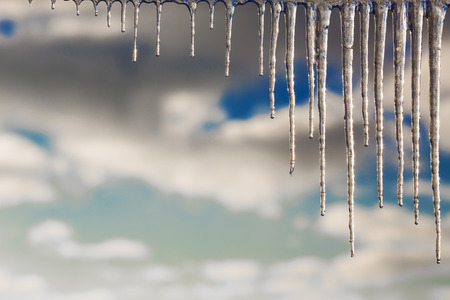 Winter icicles against the background of the cloudy sky Stock Photo