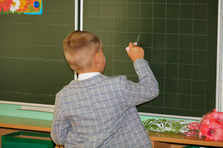 The schoolboy writes with chalk on a board at school