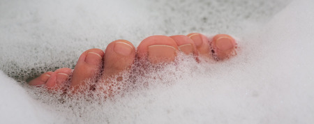 Woman spa a pedicure of legs in soap water
