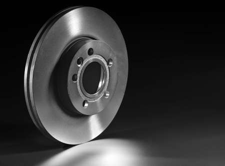 frenos: disco de freno sobre un fondo negro Foto de archivo