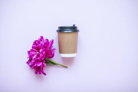 A brown takeaway coffee cup and fuchsia peony flower. Flat lay. Lay out.