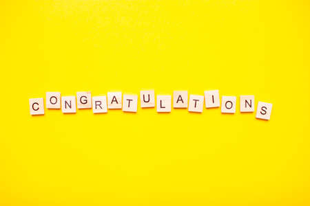 The inscription congratulations made of wooden blocks on a light yellow background.