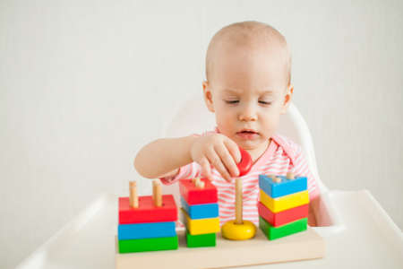 little girl plays with an educational toy - a multi-colored wooden pyramid. Development of fine motor skills and logical thinking. High quality photo