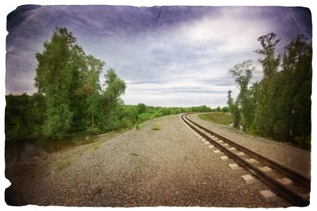 grunge image of railway in the forest near the lake on the background of the cloudy sky photo